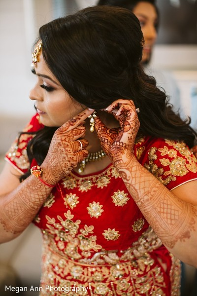 Indian bride putting her earrings capture.