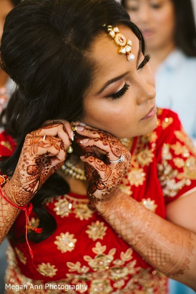 Dazzling indian bride getting her earrings on.