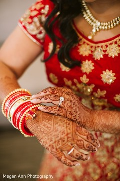 Sweet indian bride putting bangles on.