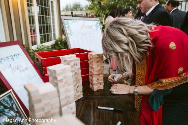 Indian wedding guest signing a Jenga block.