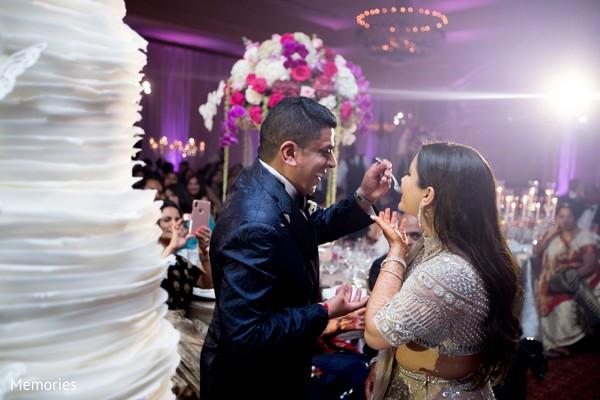 Maharani and groom sharing a slice of cake