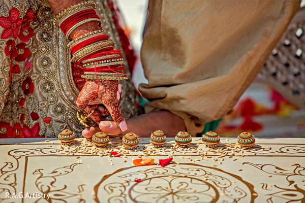 Indian groom touching the nuts with his toes ritual.