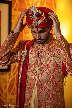 Indian groom putting his turban on.