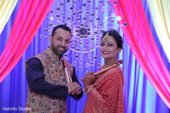 Joyful Indian couple posing at their sangeet stage.