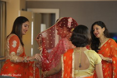Indian bridesmaids helping bride getting ready.