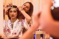 Indian bride putting her matha patti on.