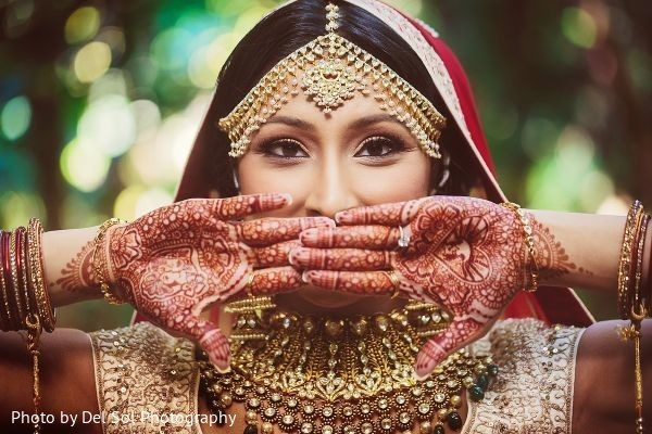 Indian bride with mehndi art, tikka, kundan and engagement ring.