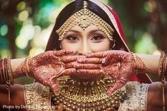Indian bride with mehndi art, tikka, kundan and engagement ring.