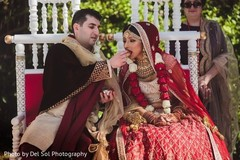 Gorgeous Indian groom giving food to bride.