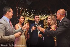 Indian couple having cheers with guests.