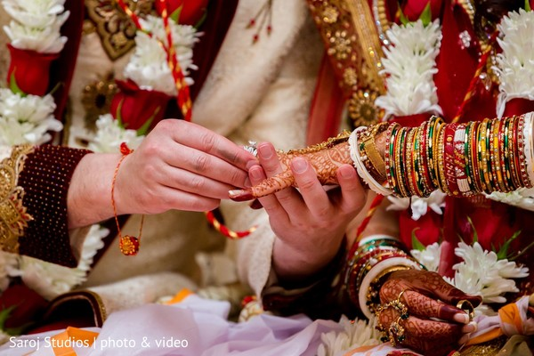 Indian groom placing the ring on Maharani
