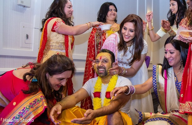 Indian groom smeared with yellow turmeric paste.