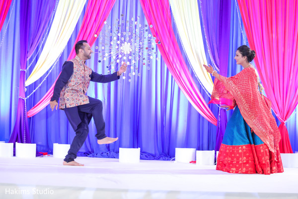Indian bride and groom dancing at sangeet stage.