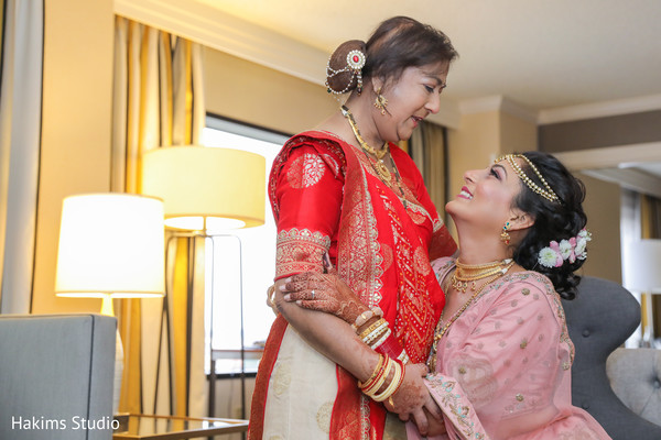 Sweet indian bride's mother helping her to get ready.