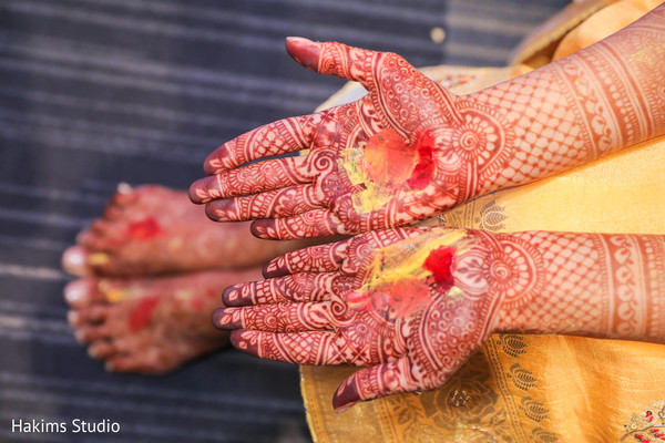 Maharani's hands with turmeric paste yellow and red.