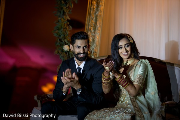 Joyful indian bride and groom at reception speech.