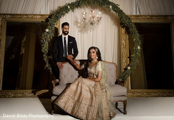 Adorable Indian bride and groom posing at reception stage.