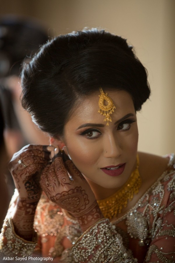 Gorgeous Indian bride putting her earrings on.