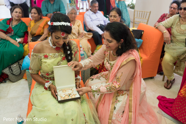 Indian bride receiving a gift at her pre-wedding party.