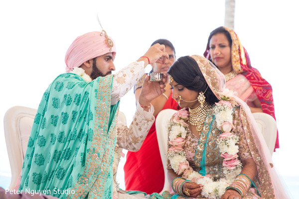 Indian groom putting the mark on maharani's forehead.