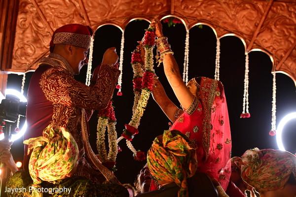 Indian couple exchanging garlands capture.
