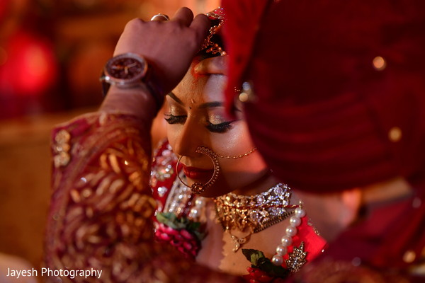 Indian groom putting the red mark on bride's forehead.