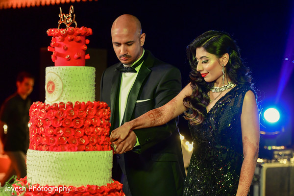 Indian bride and groom cutting cake moment.