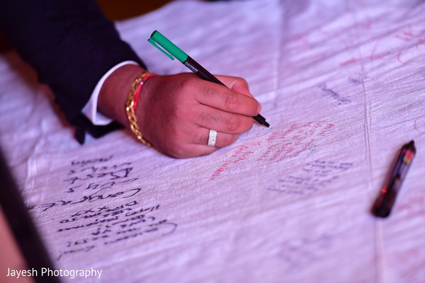 Indian wedding guest signing guest book.