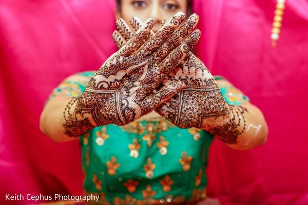 Close up capture of maharani's mehndi in hands.