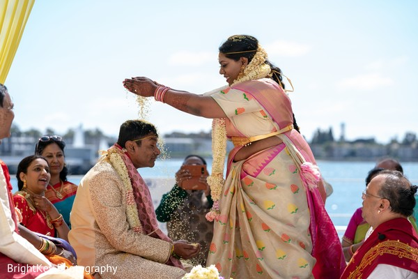 Indian bride  pouring rice onto Indian groom.
