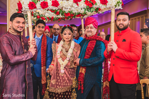 Indian bride with groomsmen entering her ceremony.
