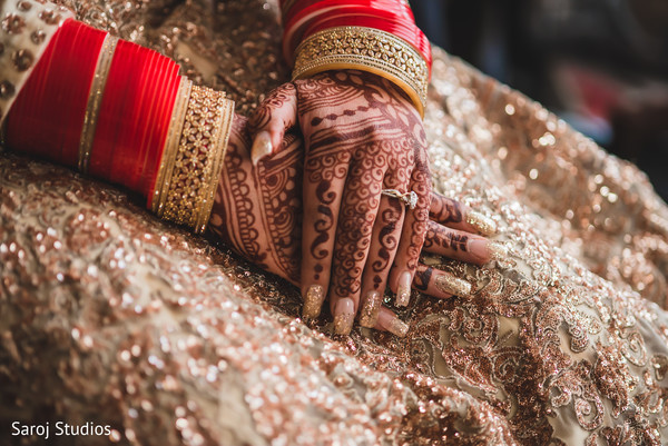 Maharani's hands with ceremony jewelry and mehndi capture.