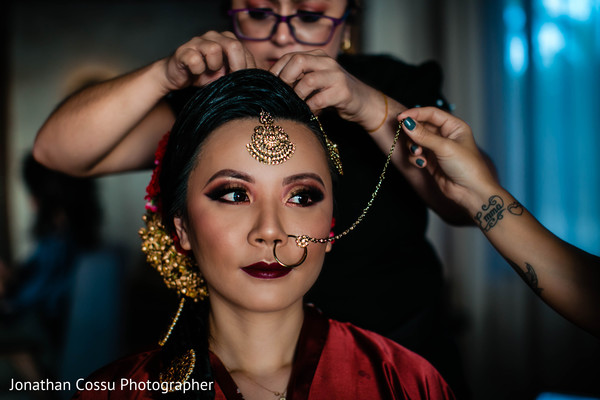 Enchanting Indian bride getting her nose ring on.