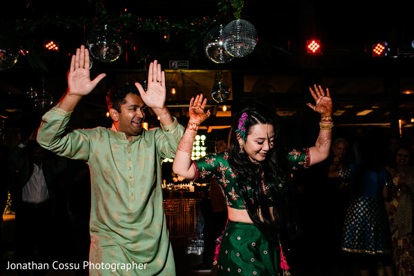 Indian lovebirds dancing at sangeet party.