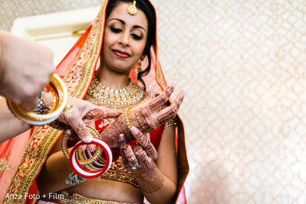 Sweet Indian bride putting her chooras on.