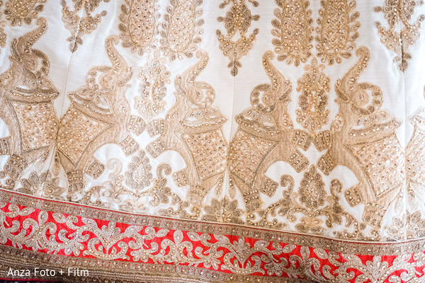 Closeup capture of maharani's golden lehenga elephants embroidery.