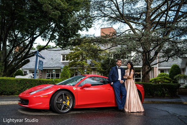 Bride and groom posing outdoors with car