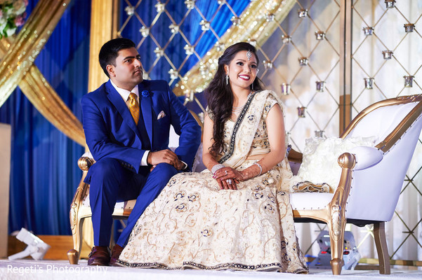 Indian couple listening to their wedding speech.
