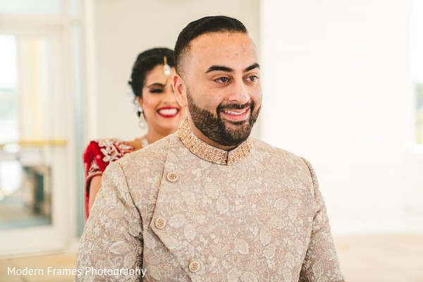 Joyful Indian groom meeting his bride for the first look.