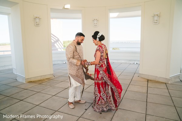 Indian groom admiring bridal mehndi art.