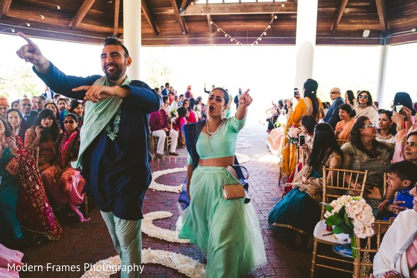 Glamorous Indian bridesmaid walking  in with groomsmen.