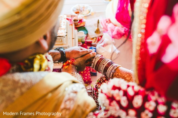 Indian groom holding bride's hands at wedding ritual.