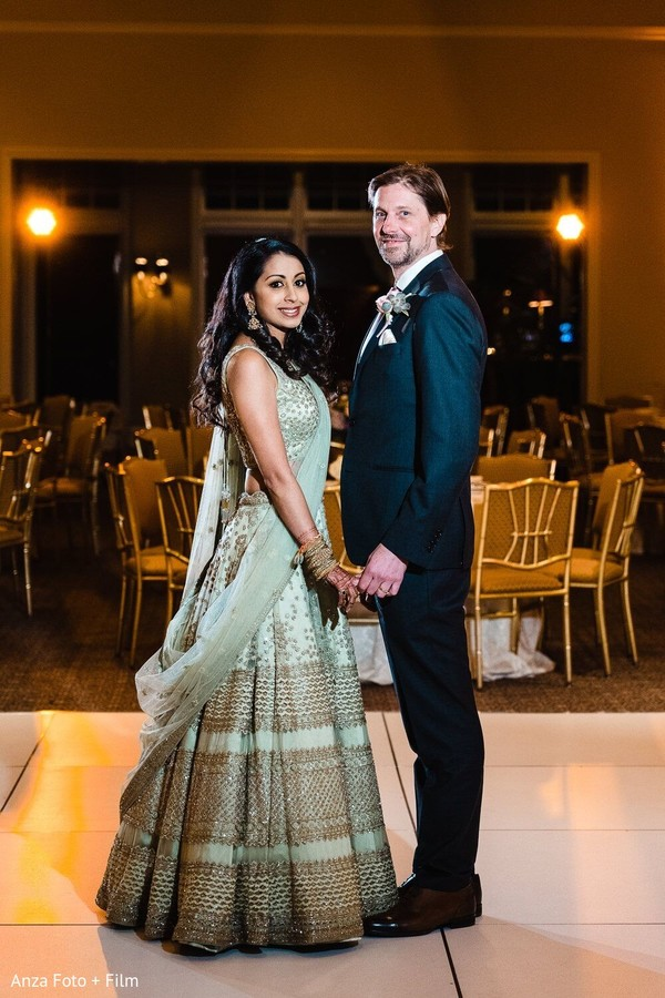 Elegant Indian bride and groom at reception party capture.