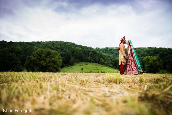 Charming Indian groom kissing bride capture.