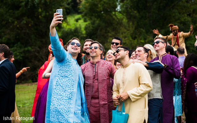 Indian groomsmen taking a selfie at baraat procession.