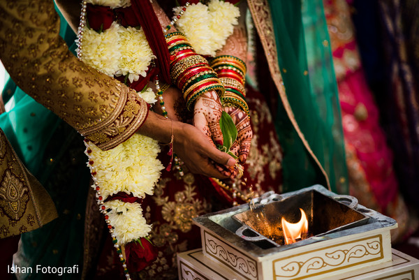 Indian couple pouring offerings to sacred fire.