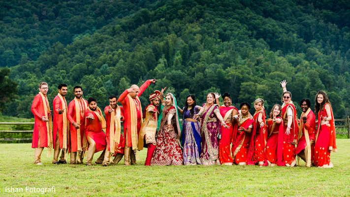 Upbeat indian bride and groom with bridesmaids and groomsmen capture.