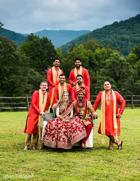 Indian lovebirds posing outdoors with groomsmen.