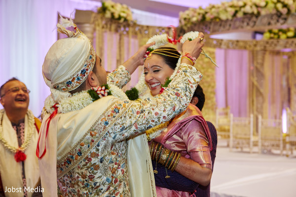 Indian groom putting garland to bride photo.