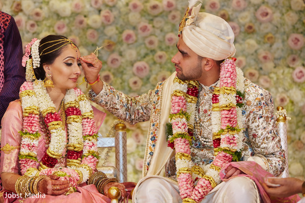 Indian groom putting the Bottu on bride's forehead.